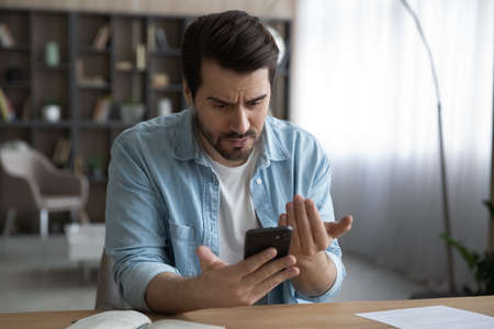 Close up unhappy dissatisfied businessman looking at phone screen, reading bad news in message, confused young male having problem with broken or discharged device, data loss or software failure