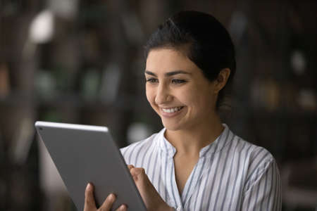 Close up smiling Indian woman having fun with tablet, holding gadget in hands, typing, looking at screen, chatting in social networks or shopping online, browsing apps, writing message, scrolling 版權商用圖片