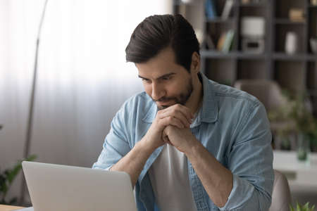 Close up irritated confused businessman looking at laptop screen, having problem with broken or discharged device, annoyed young man received bad news, unexpected debt or mistake in project 版權商用圖片