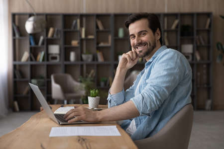 Portrait smiling successful businessman sitting at desk with laptop, confident happy entrepreneur looking at camera, positive man student or freelancer working online on project, profile picture