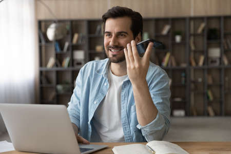 Smiling businessman recording audio voice message on smartphone, speaking, sitting at work desk with laptop, positive young man chatting online by speakerphone, activating digital assistant on gadget