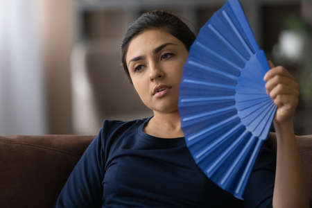 Close up overheated Indian woman waving paper fan, feeling discomfort, suffering from heat stroke at home, enjoying fresh air, sweaty young female cooling in hot summer weather without conditioner