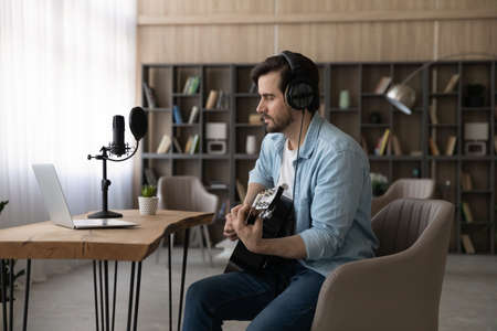 Confident man in headphones playing acoustic guitar, looking at laptop screen, sitting at desk with microphone, musician artist recording new song in home studio, student practicing, online course 版權商用圖片