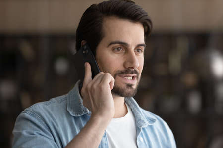 Close up smiling man talking on smartphone, answering or making call, chatting with friend, enjoying pleasant conversation, confident businessman discussing project with colleague by phone 版權商用圖片