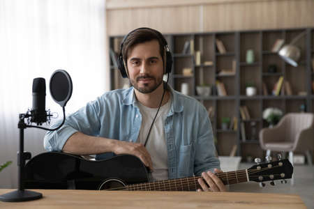 Portrait man in headphones holding guitar, looking at camera, sitting at desk in home studio, using professional microphone, musician artist recording new song or podcast, teacher shooting lesson 版權商用圖片