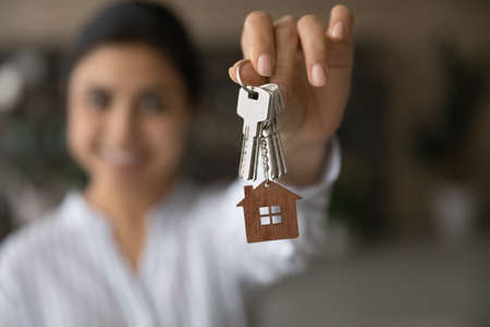 Close up focus on keys with keychain, excited tenant rejoicing relocation, satisfied customer purchasing new own apartment, Indian young woman excited by moving day, mortgage or rent concept