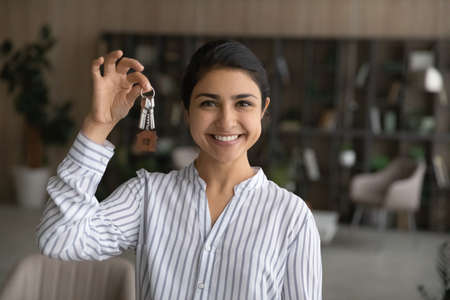 Head shot portrait smiling Indian young woman showing keys, rejoicing relocation into first new own apartment, satisfied client tenant renter celebrating moving day, mortgage or rent concept