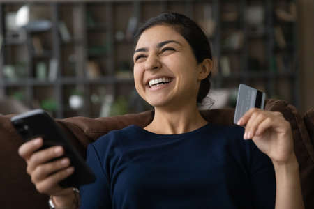 Close up overjoyed Indian woman using smartphone, internet banking service, paying online at home, holding plastic credit card, happy young female shopping, excited by sales or money refund
