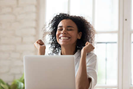 Overjoyed smiling young african ethnicity female employee feeling excited of reading email on computer with amazing news, celebrating success or achievement, job promotion, career opportunity concept. 版權商用圖片