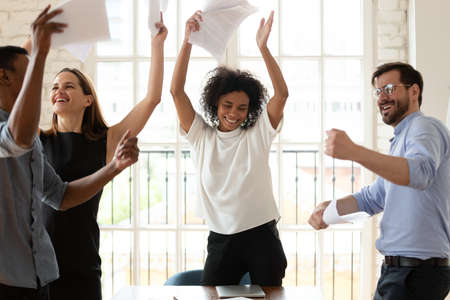 Happy young african american female team leader having fun with multiracial colleagues, dancing to energetic disco music, throwing papers in air, celebrating business success or achievement together.