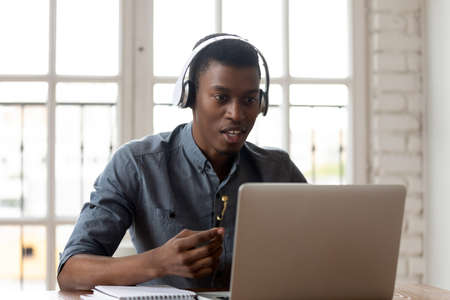 Young african american male employee colleague in wireless headphones looking at computer screen, involved in negotiating project at online meeting using video call zoom application in office.