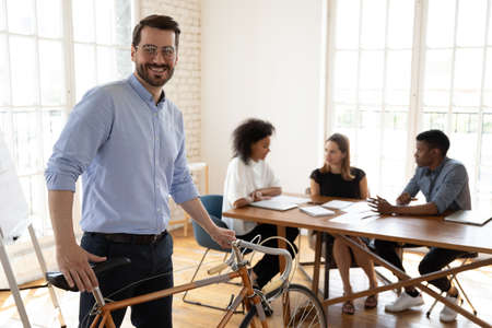 Happy young male manager in eyeglasses holding bicycle, looking at camera, enjoying healthy sporty lifestyle, coming to modern office with multiracial people involved in project negotiations.