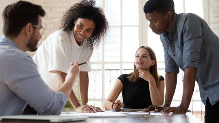 Skilled young caucasian male manager sharing project problems solutions ideas or development strategy with happy motivated interested multiracial colleagues at briefing meeting in modern boardroom.