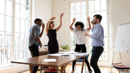 Overjoyed millennial diverse mixed race business people dancing in modern office, celebrating shared corporate success. Emotional happy multiracial employees having fun, relaxing together at workplace