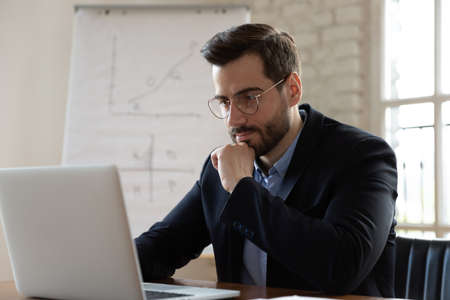 Thoughtful young male ceo executive manager in eyeglasses working on successful online project, solving problem solution, stack with difficult task, using computer software applications in office. 版權商用圖片