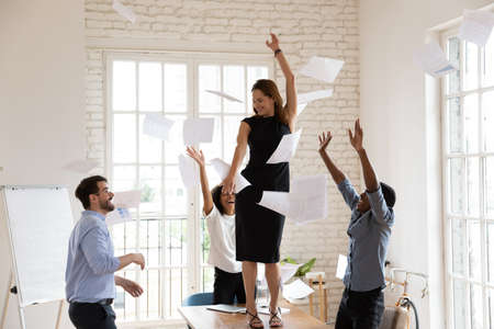 Joyful young female team leader boss dancing on table, having fun with diverse multiracial colleagues in modern office. Happy laughing mixed race employees throwing papers in air, celebrating success. 免版税图像