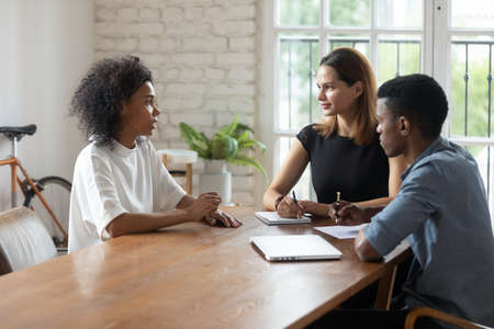 Concentrated young african female job seeker holding interview with two professional mixed race hr managers, discussing working experience at office meeting, first impression, employment concept.