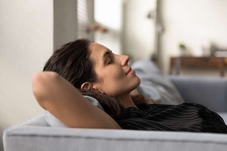 Relaxing alone. Serene carefree young latin female nap on soft cozy couch at home has pleasure breath fresh ventilated air in living room. Peaceful millennial woman meditating on sofa with closed eyes Banque d'images