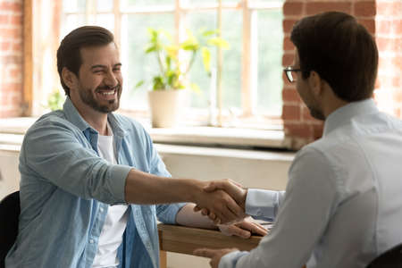 Hr manager employer shaking happy successful candidate hand at meeting, congratulating with job offer or promotion after interview, business partners handshake at meeting in office, making deal