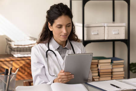 Tablet in doc job. Young latin woman in white coat medical lab worker use pad study resent clinical research results on website. Female doctor work on digital tab online check messages in ehealth app