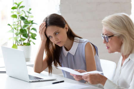 Unhappy young female employee bored with middle-aged colleague discuss paper document at meeting. Tired woman worker bothered annoyed by senior coworker lecture about paperwork at team briefing.