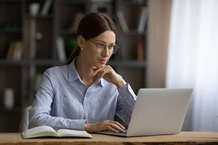 Online business. Focused young lady in glasses sit at home office engaged in computer job read information on laptop screen. Thoughtful millennial woman chat in corporate network type email text on pc