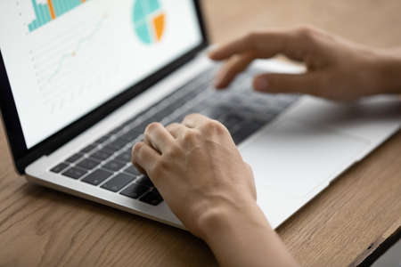 Managing project performance. Close up of woman manager hands type on laptop keyboard prepare business analytic report via online service. Marketing specialist work with sales infographic on pc screen