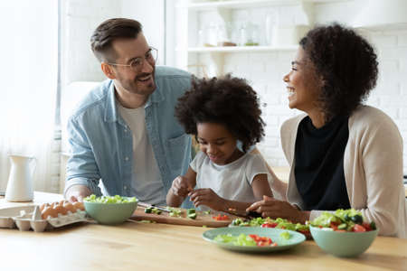 Overjoyed young multiethnic family with little biracial daughter have fun cook healthy salad at home together. Smiling multiracial mom and dad and small ethnic child prepare food. Diversity concept.