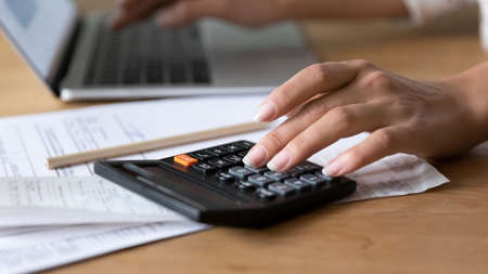Close up young woman using calculator, managing household budget, counting paper bills or taxes, managing monthly budget, doing financial paperwork alone at home, accounting bookkeeping concept.