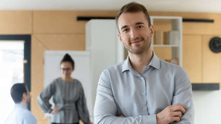 Head shot portrait of confident businessman executive owner standing in office with arms crossed, successful young man employee intern worker looking at camera, posing for corporate photo alone Stock fotó