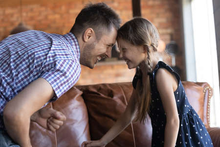 Happy excited preschooler girl playing active games with daddy at home, practicing funny fight, touching foreheads, smiling and laughing. Dad and daughter enjoying family activities, having fun Standard-Bild