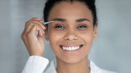 Face portrait of happy Black millennial girl plucking brows with tweezers smiling at camera despite painful procedures. Young woman tweezing eyebrows and correcting shapes at home. Close up