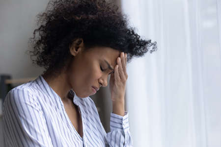 Unhappy young African American woman feel depressed sad crying alone at home. Upset millennial mixed race female distressed with bad negative news, suffer from problems misfortune or failure. Stock Photo