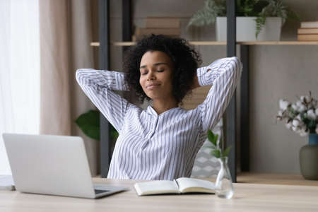 Calm millennial African American businesswoman relax at desk at home office breathe fresh air. Young mixed race woman sit at table work on computer take nap or sleep, relieve negative emotions.