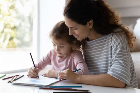 Loving young Latino mother and small teen biracial daughter drawing painting together at home. Happy caring Hispanic mom and little ethnic girl child have fun play engaged in hobby activity.