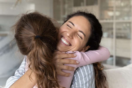 Cute small ethnic girl child hug cuddle smiling young Hispanic mother show love and care in relations. Little biracial daughter embrace Latino mom make peace reconcile. Family unity concept.