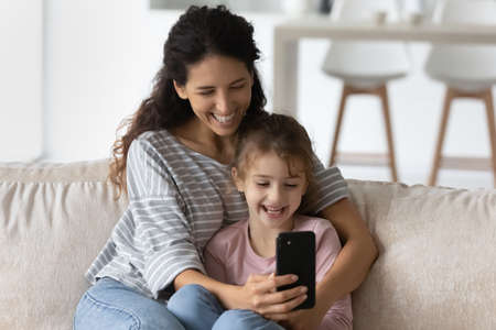 Overjoyed young Latino mother and daughter use cellphone look at screen laugh watch funny video online. Smiling Hispanic mom and small girl child talk speak on webcam virtual event on smartphone. Banque d'images