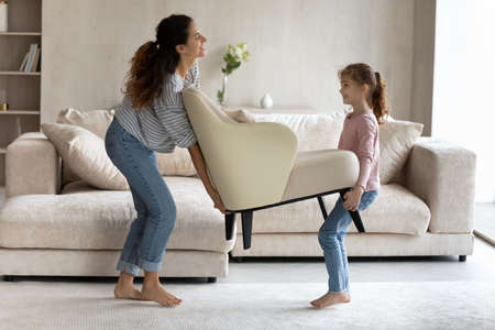 Smiling young single Hispanic mother and teen daughter carry armchair settle in new own home. Happy Latino mom and teenage girl child decorate cozy living room. Moving, relocation concept.