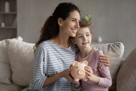 Happy young Hispanic mom and small daughter hold piggybank take care of family budget finances together. Smiling Latin mother and teen child recommend savings or money investment. Banking concept. Banque d'images