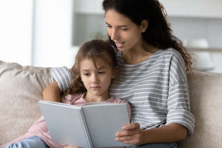 Loving young Latino mother read book to small teen ethnic daughter relax together on couch in living room. Caring Hispanic mom and little girl child rest at home enjoy story or novel. Hobby concept. Banque d'images