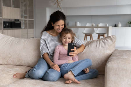 Smiling young Hispanic mother and teen daughter relax on sofa at home talk speak on video call on cellphone. Happy Latino mom and little girl child have fun use smartphone have webcam online event.
