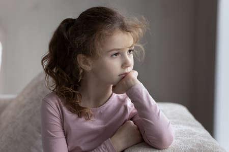 Sad little teen biracial girl child look in distance feel lonely abandoned lack communication. Unhappy small ethnic kid suffer from discrimination bullying, have problems. Loner, outcast concept. Banque d'images