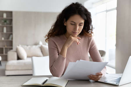 Pensive young Hispanic woman sit at desk at home office work online on computer read paperwork documents. Millennial Latino female use laptop consider financial report or paper correspondence.