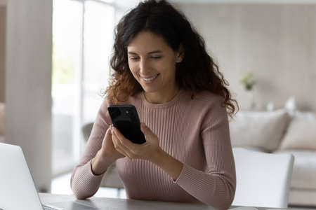 Happy Hispanic young woman sit at desk look at cellphone screen text message online on modern gadget. Smiling Latino millennial female use smartphone talk speak on video call on device at home.