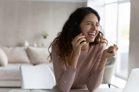 Overjoyed millennial Hispanic woman talk speak on cellphone laugh and joke. Smiling young Latino female have pleasant smartphone call on modern gadget, use mobile provider connection on device.