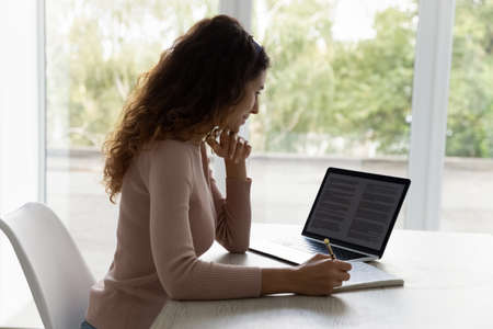 Young Hispanic woman in headphones sit at desk at home office work online on computer gadget making notes. Millennial Latino female in earphones study distant on laptop writing. Education concept. Banque d'images