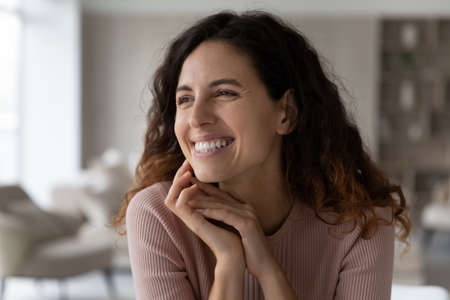 Close up of happy millennial Hispanic woman look in distance dreaming thinking of opportunities perspectives. Smiling young Latino female imagine visualize achievements. Vision, dreamer concept. Banque d'images