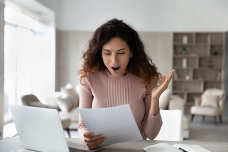 Happy excited Latino woman shocked by good news in paper correspondence working online on laptop at home office. Overjoyed stunned Hispanic female surprised by notice or paperwork notification.