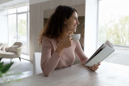 Smiling young Latino woman sit at desk at home read book drink coffee or tea enjoying sunny leisure day. Happy millennial Hispanic female relax rest indoors with cup. Hobby, weekend concept. Banque d'images
