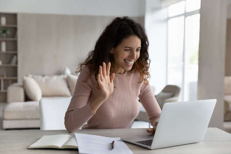 Smiling Hispanic woman work online on computer at home greet wave talk speak on video call on device. Happy Latino female use laptop have webcam video virtual event with client or teacher.